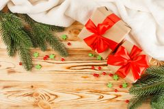 Craft gift boxes with red ribbon and bow, green Christmas tree, decorations, white plaid on wooden background. Xmas and New Year c Stock Image