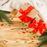 Craft gift boxes with red ribbon and bow, green Christmas tree, decorations, white plaid on wooden background. Xmas and New Year c Royalty Free Stock Images