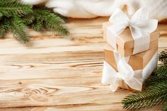 Craft gift boxes with white ribbon, bow, green Christmas tree, decorations, white plaid on wooden background. Xmas and New Year co stock photos