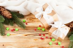 Craft gift boxes with white ribbon, bow, green Christmas tree, decorations, white plaid on wooden background. Xmas and New Year co Stock Images