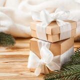 Craft gift boxes with white ribbon, bow, green Christmas tree, decorations, white plaid on wooden background. Xmas and New Year co Stock Photo