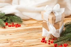Craft gift boxes with red ribbon and bow, green Christmas tree, decorations, white plaid on wooden background. Xmas and New Year c royalty free stock photos