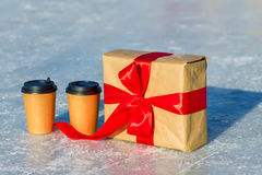 Craft gift with red ribbon and cups of coffee on the ice rink.  Stock Image
