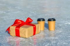 Craft gift with red ribbon and cups of coffee on the ice rink.  Royalty Free Stock Image