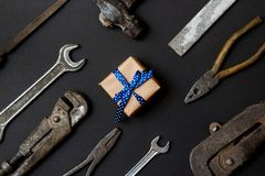 Craft gift with vintage old tools on black paper background. Fathers day concept. Flat lay stock photos