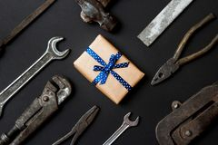 Craft gift with vintage old tools on black paper background. Fathers day concept. Flat lay royalty free stock images