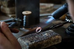 Craft jewelery making with flame torch stock images