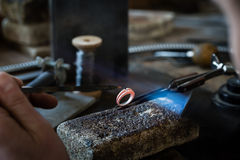 Craft jewelery making with flame torch. Jeweler working on wedding gold ring in his workshop. Craft jewelery making with flame torch royalty free stock image