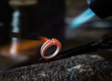Craft jewelery making with flame torch. Jeweler working on wedding gold ring in his workshop. Craft jewelery making with flame torch royalty free stock photo