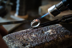 Craft jewelery making with flame torch. royalty free stock photography