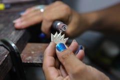 Craft jewelery making. Crown pendant polishing. Stock Photo