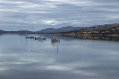 Craft moored in Dunalley inlet on overcast day royalty free stock photography