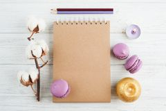 Craft notebook with purple macarons. Open empty craft notebook with purple macarons, pencils and lit candles. Flat lay, top view concept royalty free stock images