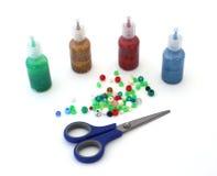 Craft paints, beads, scissors. Craft materials over white - scissors, glitter paint, beads Stock Photo