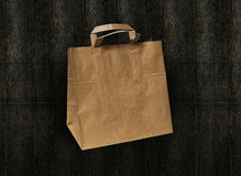 Craft paper bag isolated on dark wooden background Stock Photography
