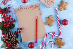 Craft paper card and decoration on blue table top view. Christmas mockup for greeting, plans, wishes, goals. Flat lay. Merry Chraistmas and happy new year 2019 royalty free stock photos
