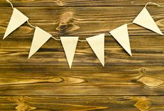 Craft paper  flags  party garland  on wooden background.  Stock Photography