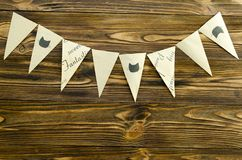 Craft paper  flags  party garland  on wooden background.  Royalty Free Stock Image