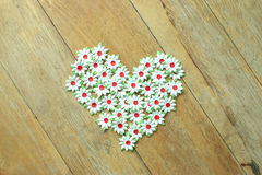 Craft of paper flower placed a heart of Love on wood floor. Royalty Free Stock Photography