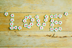 Craft of paper flower placed a letter of Love word on wood floor. Royalty Free Stock Photo