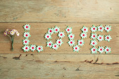 Craft of paper flower placed a letter of Love word on wood floor. Stock Photos