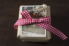 Craft paper gift box, old photograph. red plaid ribbon Royalty Free Stock Photos