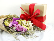 Craft paper gift box with ribbon bow and flower. Bouquet with fabric texture Stock Image