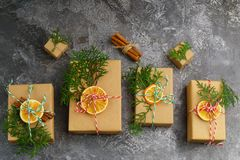 Craft Paper Presents Boxes Cord Fir Tree Branch Red Balls Dry Sliced Orange Fruit on Concrete Background. Christmas Gift Concept T stock photo