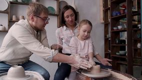 Craft person family molding pot in small workshop studio. Happy day with favorite hobby concept. Smiling family sitting on chair, using electric wheel circle and stock footage