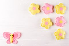 Craft pink and yellow butterfly and flowers, copyspace on white wooden background. Hand made felt toys. Abstract sky. Royalty Free Stock Image