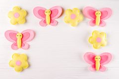 Craft pink and yellow butterfly and flowers, copyspace on white wooden background. Hand made felt toys. Abstract sky. Royalty Free Stock Images