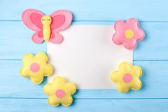 Craft pink and yellow butterfly and flowers with white paper, copyspace on blue wooden background. Hand made felt toys. Abstract s Royalty Free Stock Photography
