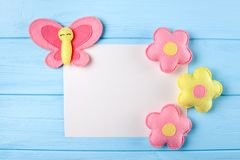 Craft pink and yellow butterfly and flowers with white paper, copyspace on blue wooden background. Hand made felt toys. Abstract s Royalty Free Stock Photo