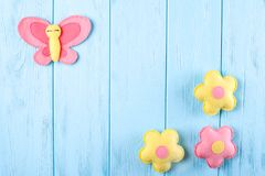Craft pink and yellow butterfly and flowers with white paper, copyspace on blue wooden background. Hand made felt toys. Abstract s Stock Images