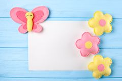 Craft pink and yellow butterfly and flowers with white paper, copyspace on blue wooden background. Hand made felt toys. Abstract s Stock Photography