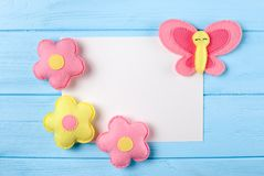 Craft pink and yellow butterfly and flowers with white paper, copyspace on blue wooden background. Hand made felt toys. Abstract s Stock Image