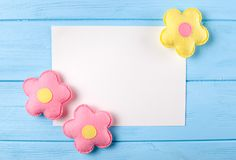 Craft pink and yellow flowers with white paper, copyspace on blue wooden background. Hand made felt toys. Abstract sky. Royalty Free Stock Photo