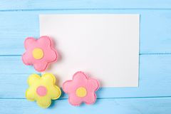 Craft pink and yellow flowers with white paper, copyspace on blue wooden background. Hand made felt toys. Abstract sky. Stock Image
