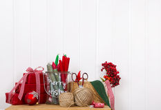 Craft supplies for red white christmas gifts on a white wall for Stock Image