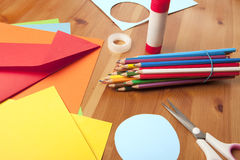 Craft table with paper and colored pencils. The table top is made of wood. on the table, scissors, colored pencils, construction paper and tape Stock Photography
