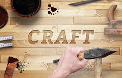 Craft word carved in wood with hammer and chisel. Stock Image