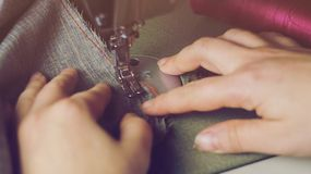 Craft workshop for tailoring. Young seamstress repairing a men`s light jacket, measuring the dimensions on a mannequin. Toning,. Close-up master and tools stock image
