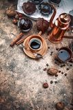 Crafting coffee in clay cup with bean. Cezve and chocolate cake top view on grunge background Royalty Free Stock Images