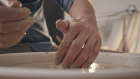 Crafting, custom-made products: ceramics and clay products. Potter at work: men`s hands, stained with clay, work with a potter`s wheel. Man-ceramist creates a stock video footage