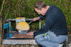 Craftman. Cutting a stone tile Royalty Free Stock Photos
