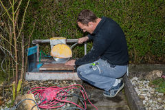 Craftman. Cutting a stone tile Stock Image