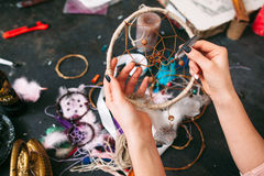 Craftman shows  Dreamcatcher. Craftswoman makes Dreamcatcher of sewing accessories. top view on workshop table and hands Royalty Free Stock Photography
