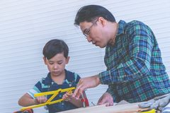 Craftman-Vater, der seinen Jungen unterrichtet, an Bauholzarbeitwerkzeugen zu arbeiten lizenzfreies stockbild
