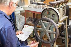 A craftman worker is looking a tax bill worry. A male worker is looking a tax bill at his jewelry workshop, worry, concerned Royalty Free Stock Photos
