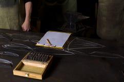 Craftmen ställning nära tabellen i smedja På den tabellinstrumentet och notepaden med den tomma sidan Arkivbilder